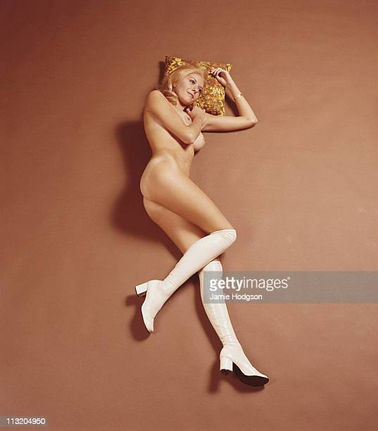 A young blonde woman in white knee boots lies naked on a studio floor circa 1970