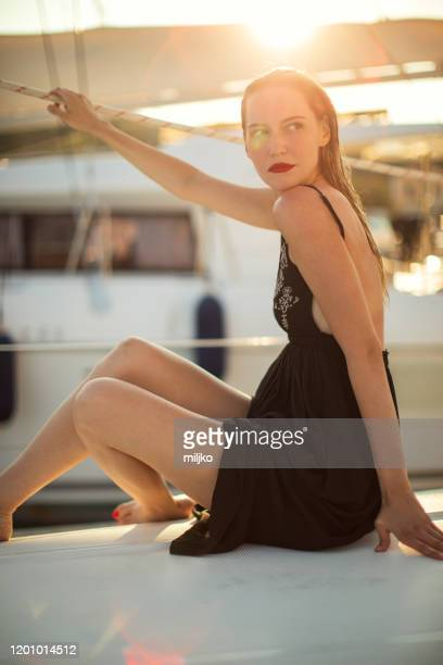 young blonde woman on sail yacht - black dress stock pictures, royalty-free photos & images