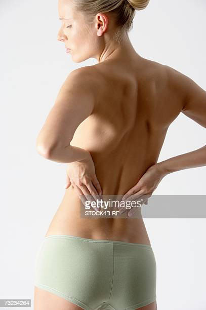 Young blonde woman only wearing a slip with her hands on her back, rear view