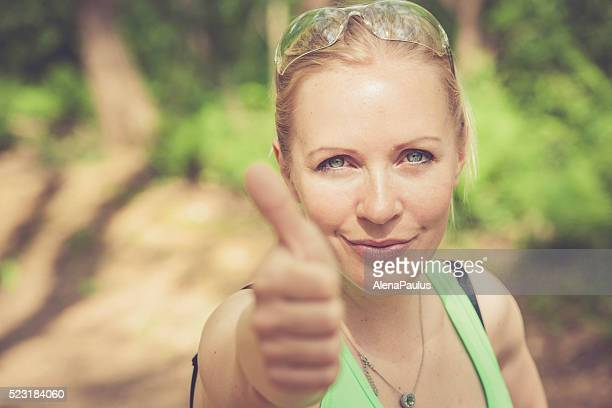 Young blonde woman outdoors in the forest, OK sign