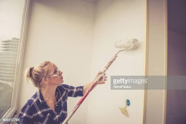 Junge blonde Frau Malerei Wand des Hauses mit einem Farbroller