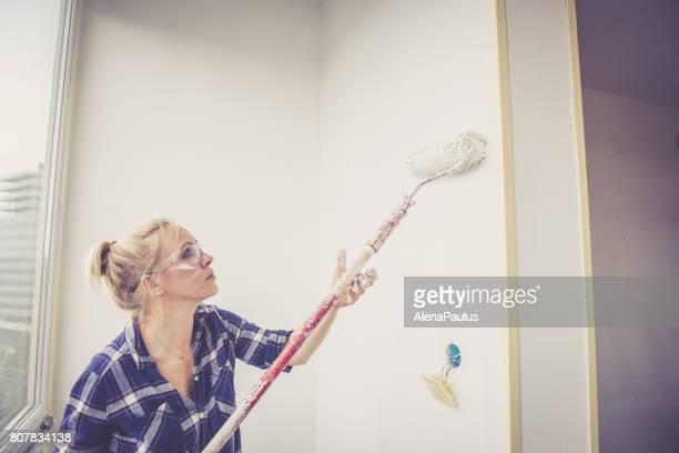junge blonde frau malerei wand des hauses mit einem farbroller - renovierung themengebiet stock-fotos und bilder