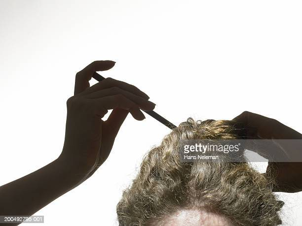 Young blonde woman placing japanese hairpin in hair bun, close-up