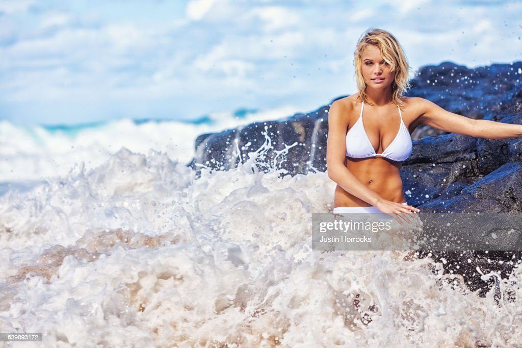 Young Blonde Woman Posing on Hawaiian Beach Among Violent Waves : Stock Photo