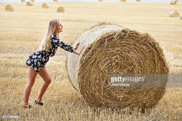 Young blonde woman pushing a bale of straw on field
