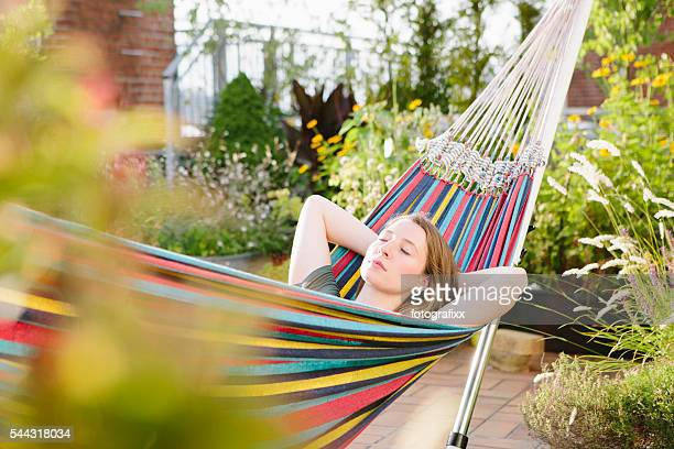 young blonde woman relax in hammock, summer, closed eyes
