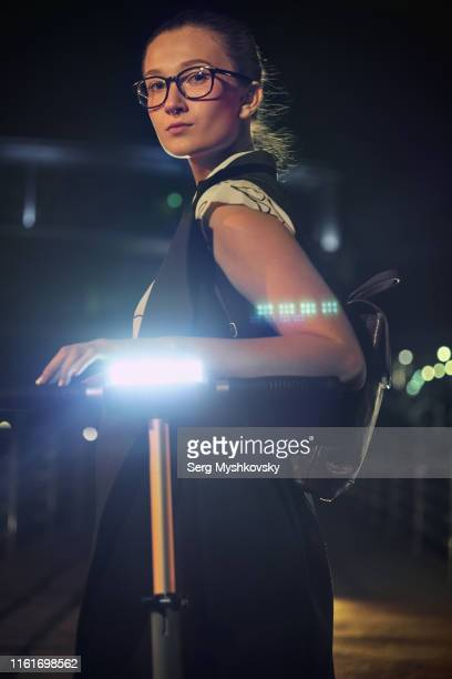 young blonde woman returning from work on an electric push scooter at night - myshkovsky stock photos and pictures