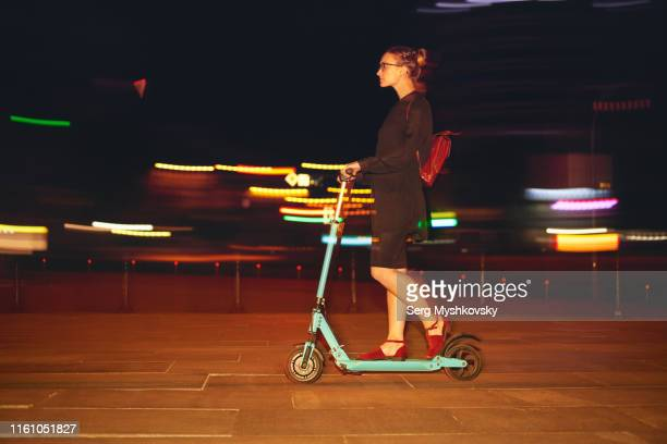 young blonde woman returning from work on an electric scooter at night - myshkovsky stock photos and pictures