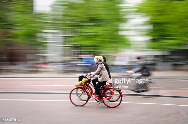 young blonde woman riding a bicycle in amsterdam, holland. - ogphoto stock pictures, royalty-free photos & images