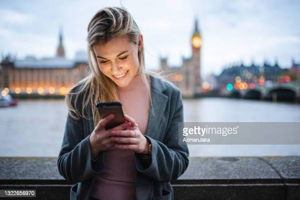 young blonde woman scrolling on her phone in front of big ben - river thames stock pictures, royalty-free photos & images