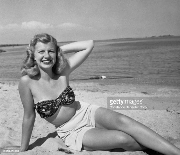 A young blonde woman siting on beach with her arm behind her head and her legs crossed USA
