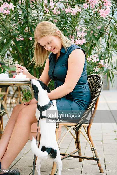 young blonde woman sits in sidewalk cafe with her dog