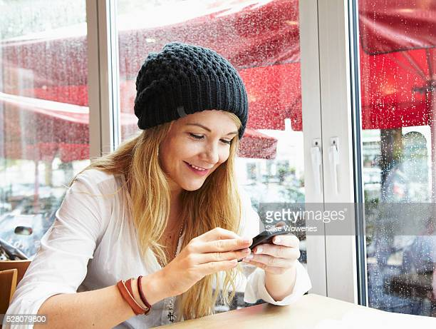 young blonde woman sitting in a cafe and writing messages - surfing the net stock pictures, royalty-free photos & images
