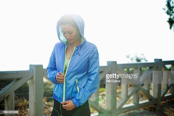 Young blonde woman standing and zipping up jacket on promenade
