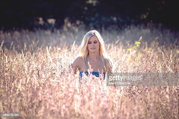 CONTENT] A young blonde woman standing in a field of high grass in the late afternoon with the warm sun behind her Bavaria 2013