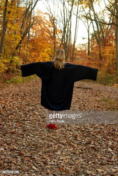 young blonde woman standing in the woods wearing an oversized black coat