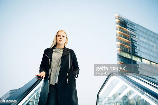 young blonde woman standing on escalator, urban background - central berlin stock pictures, royalty-free photos & images