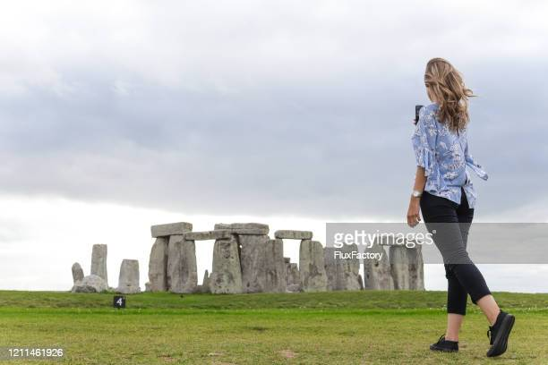 young blonde woman taking a photo of stonehenge - religious equipment stock pictures, royalty-free photos & images