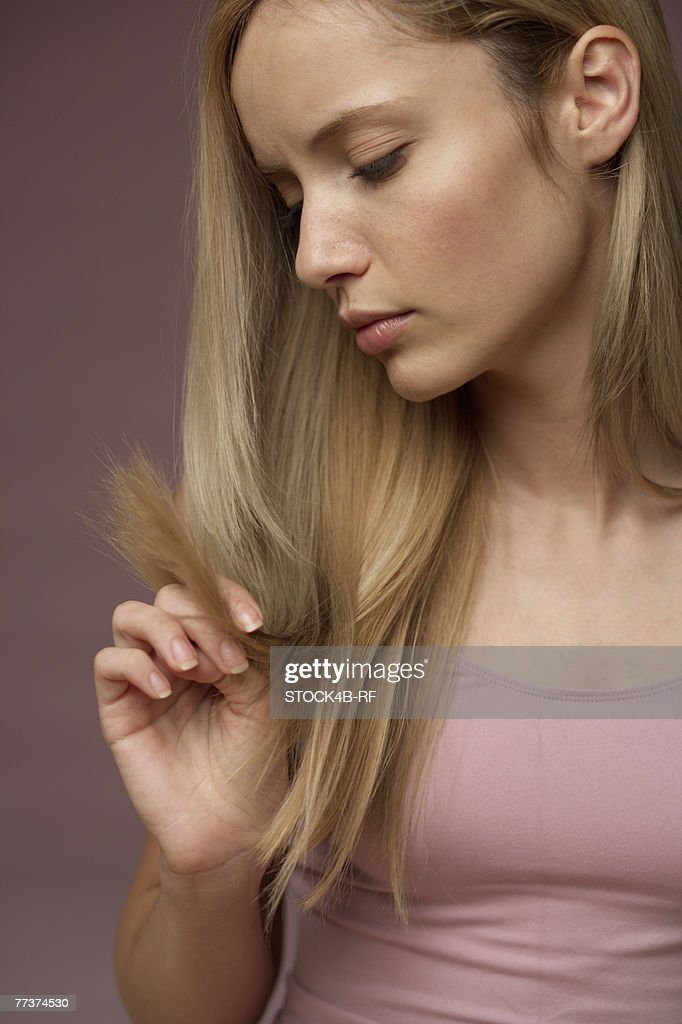 Young blonde woman unhappy about split ends of her blonde long hair : Photo