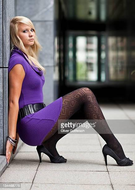 young blonde woman wearing a purple dress and high heels posing while sitting - junge frau strumpfhose stock-fotos und bilder