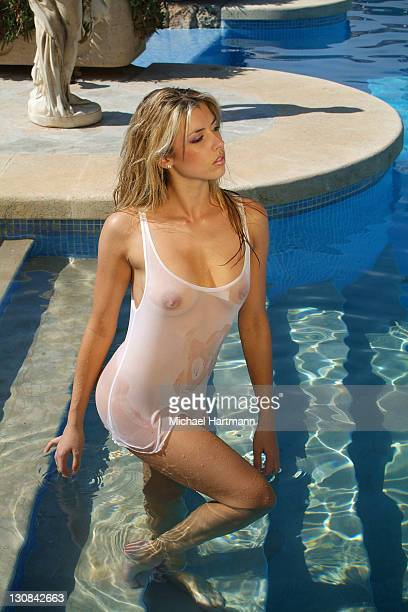 young, blonde woman wearing a wet white t-shirt standing in a swimming pool, mallorca, balearic islands, spain, europe - wet t shirts - fotografias e filmes do acervo