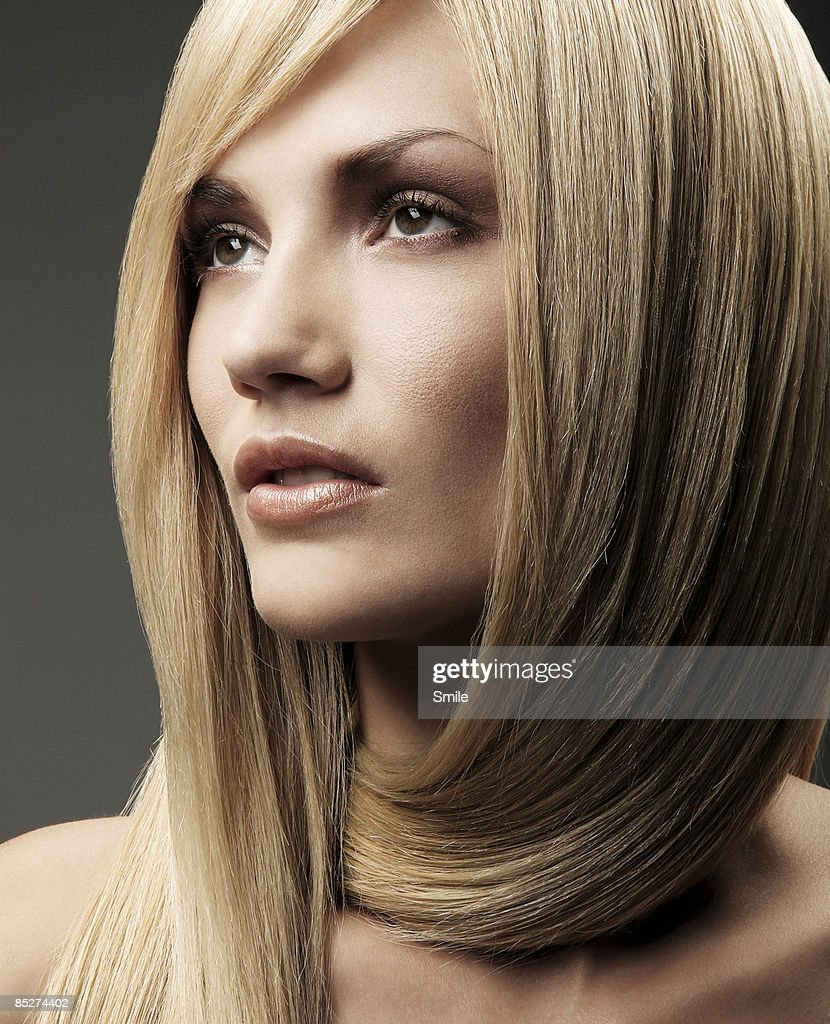 Young blonde woman with hair wrapped around neck : Stock Photo