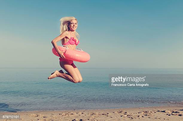 Young Blonde Woman with Pink Swimming Ring on the