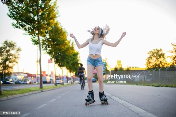 young blonde women  is riding roller scates  and listening to music - boulevard stock pictures, royalty-free photos & images