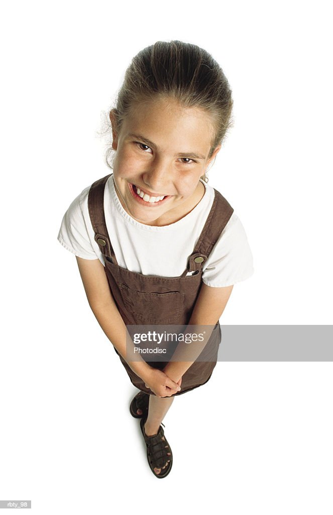 young blond-haired caucasian girl wearing brown sandals and a brown jumper over a short-sleeve white shirt crosses her hands in front of her as she peers upward through brown eyes at the camera and smiles : Foto de stock
