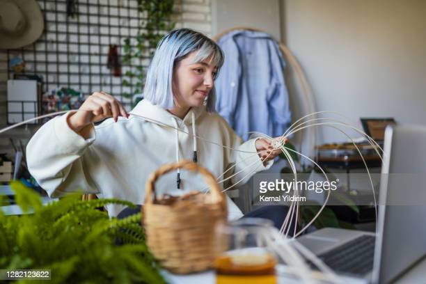 young blue haired woman knitting a wicker pot at home using laptop for watching online tutorial - individual event stock pictures, royalty-free photos & images
