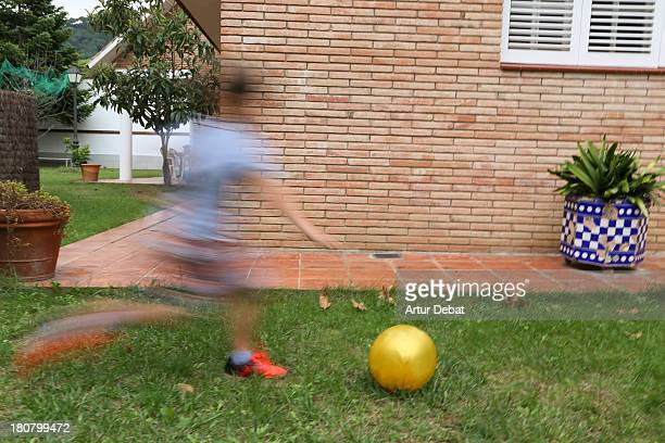 Young blurred boy playing football at backyard
