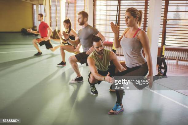 young body conscious people having trx training in a gym. - circuit training stock photos and pictures