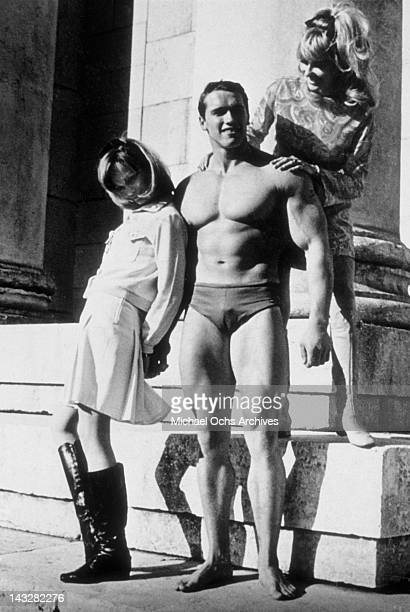 Young bodybuilder Arnold Schwarzenegger poses with some girls circa 1967 in Munich West Germany