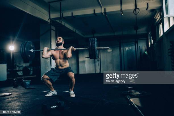 young bodybuilder exercising with barbells - snatch weightlifting stock photos and pictures
