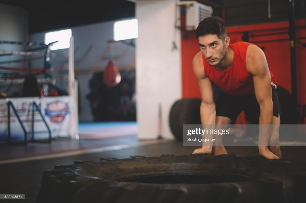 Young Bodybuilder flipping tire at the gym : Stock Photo