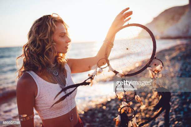 Young bohemian woman day dreaming with dreamcatcher at beach