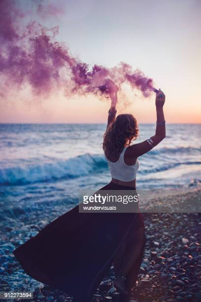 young bohemian woman partying with smoke bombs at the beach - crop top stock pictures, royalty-free photos & images