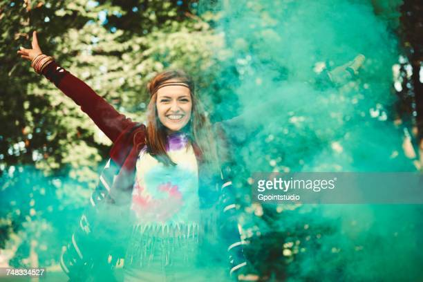 Young boho woman dancing with green smoke flare at festival