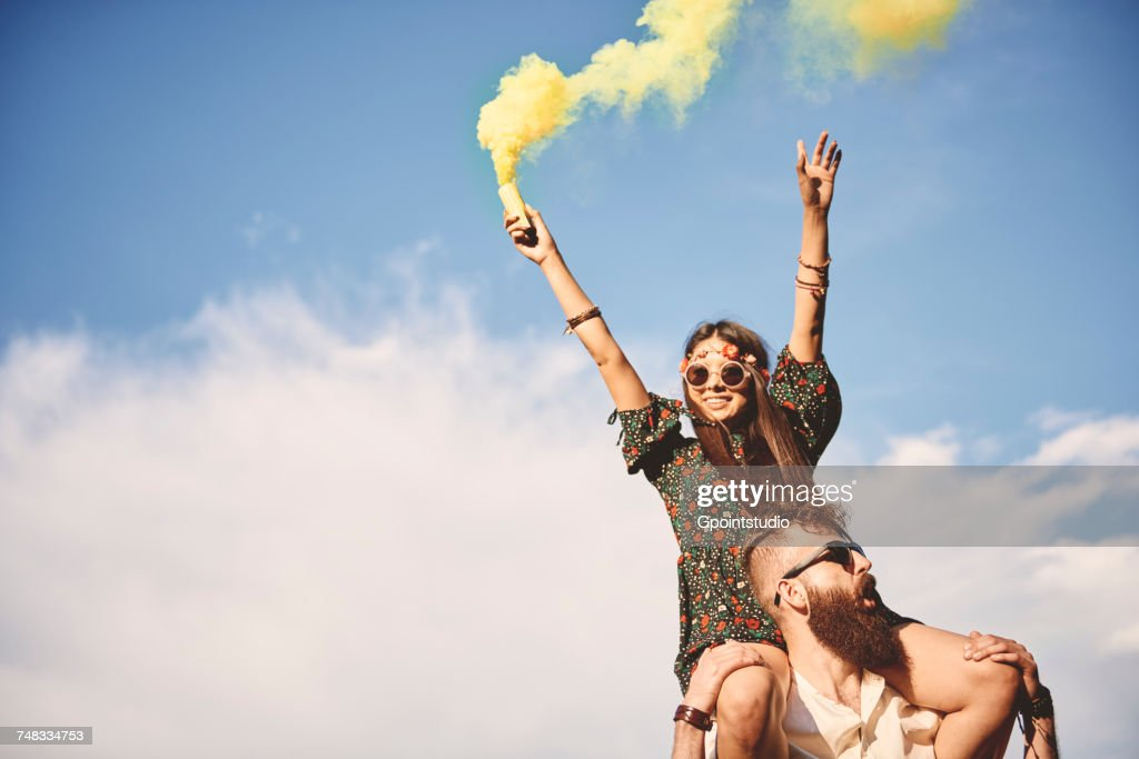 Young boho woman holding yellow smoke flare on boyfriends shoulders at festival : Stock Photo