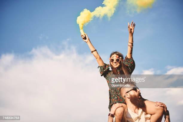 Young boho woman holding yellow smoke flare on boyfriends shoulders at festival