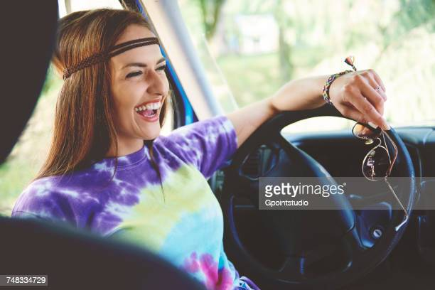 young boho woman laughing in front seat of recreational van - tie dye stock pictures, royalty-free photos & images
