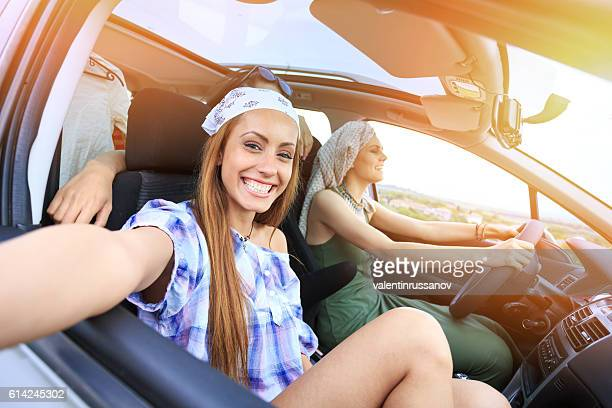 Young boho women traveling by car and making selfie