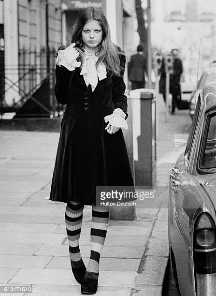 A young boutique worker sets off for work She wears a velvet coat platformheeled clogs and striped socks London 1972