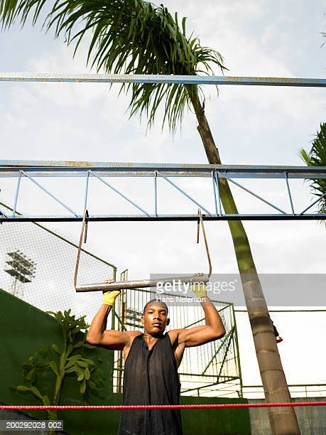 Young boxer doing pull-ups, portrait