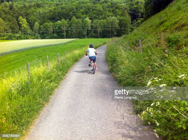 Young boy 12 years old riding his BMX bicycle on the small road in the countryside