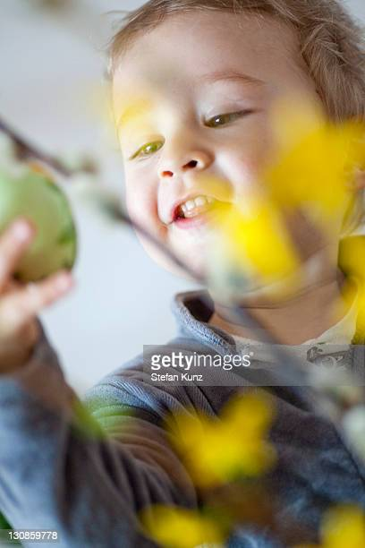 young boy, 18 months, looking at an easter egg - happy resurrection day stock pictures, royalty-free photos & images