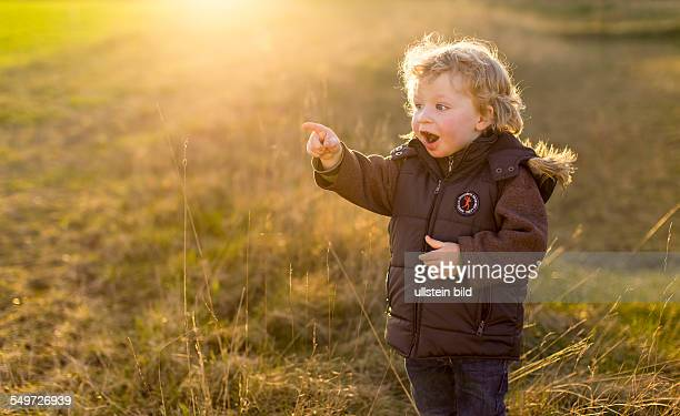 Young boy 2 years pointing surprised to the left in the sunset on a meadow