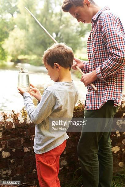 Young boy 7-9 looking at fish in jam jar