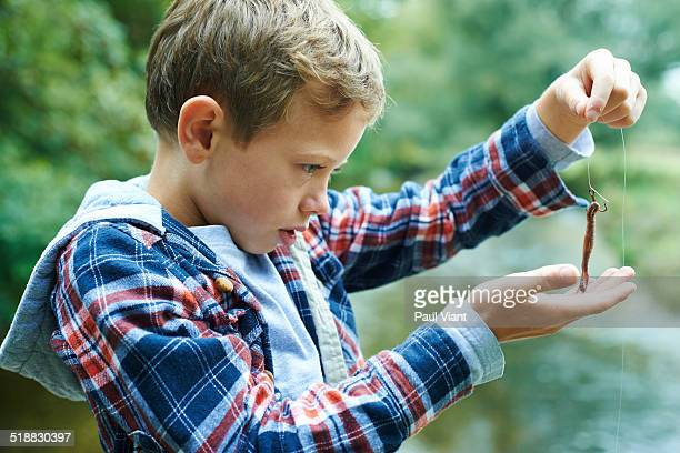 Young boy 7-9 studying worm on fish hook