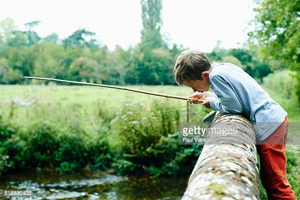 Young boy 8-10 leaning over bridge fishing